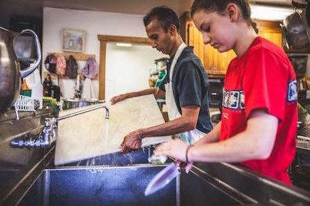 middle schooler and teacher washing dishes